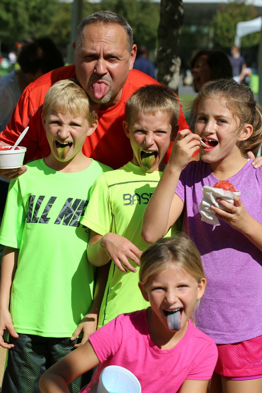 Family sticking out tongues after eating a snow cone