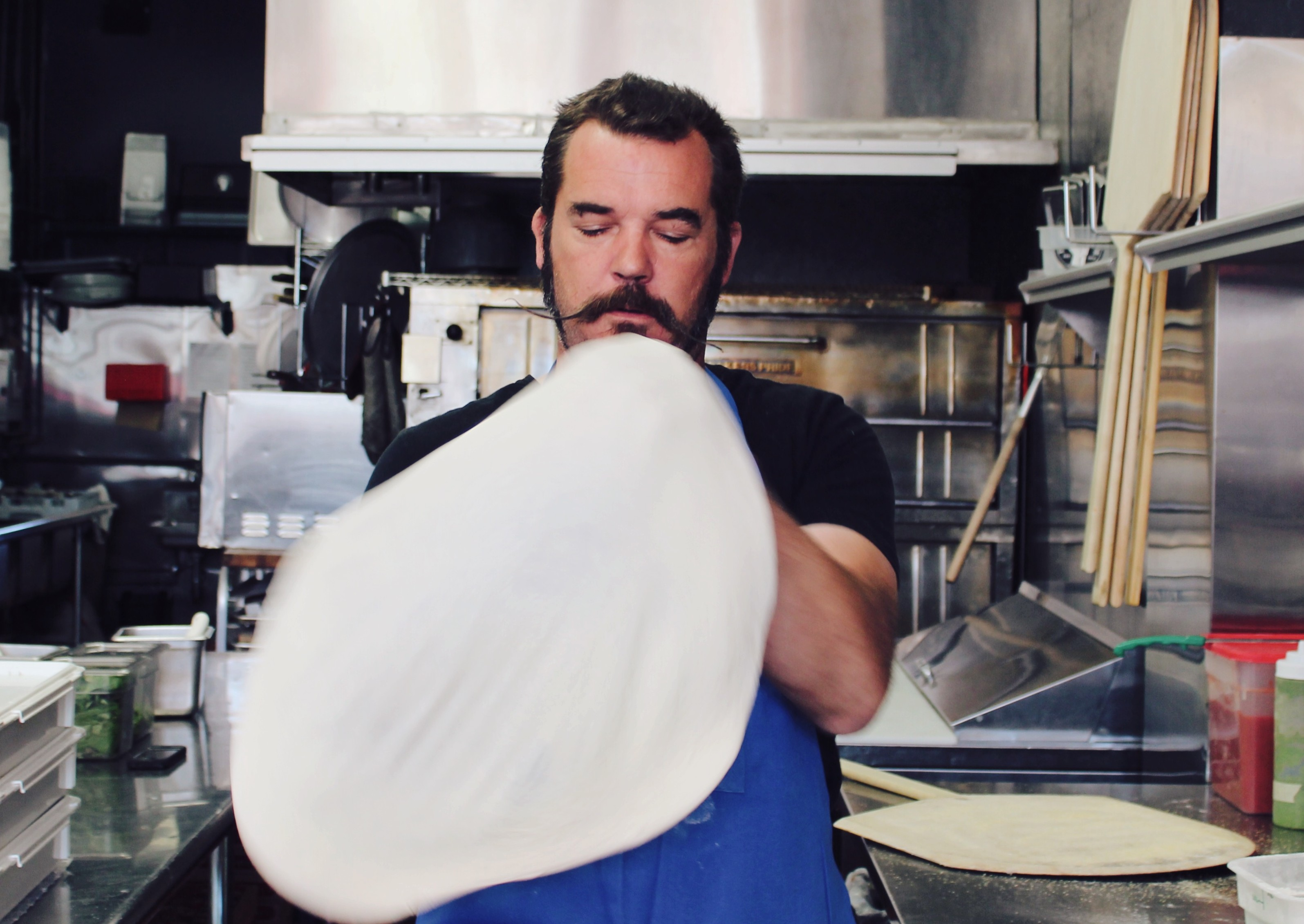 Owner James Whitehead tossing fresh pizza dough