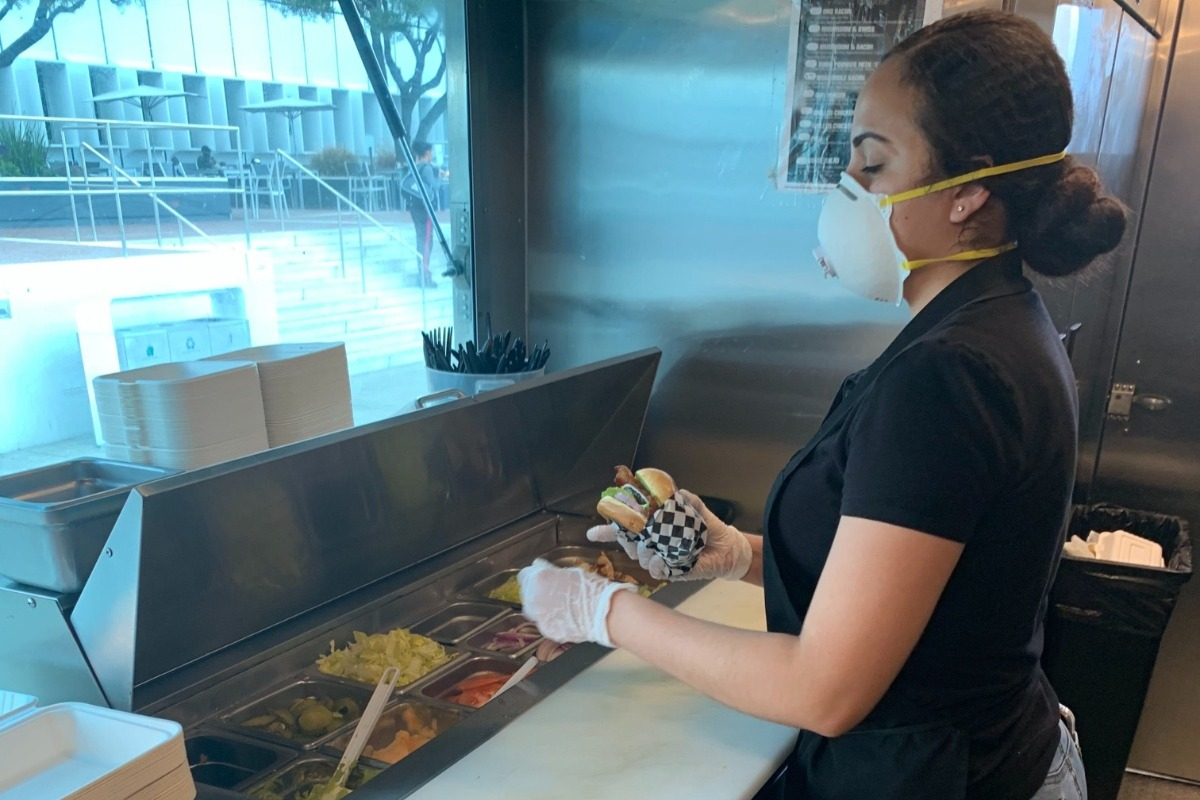 woman prepares food wearing face mask during covid-19 crisis